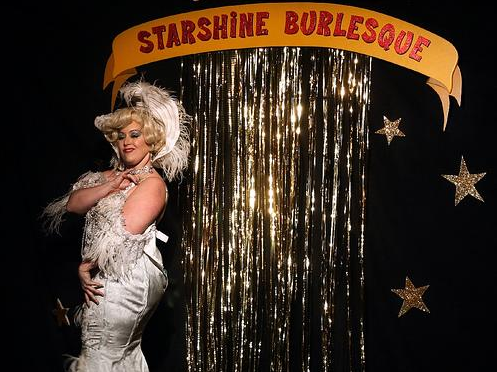 Dirty Martini rocking it out in front of the gold mylar curtain of Starshine Burlesque