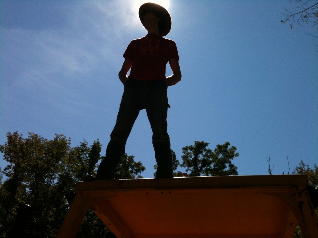 Burke Heffner stands on top of a vintage truck on the road.
